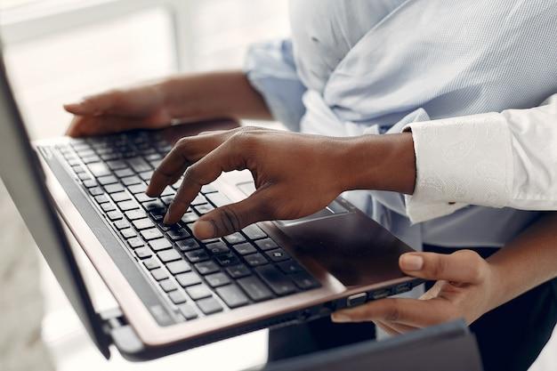 Schwarze, die auf einer weißen wand mit einem laptop stehen Kostenlose Fotos