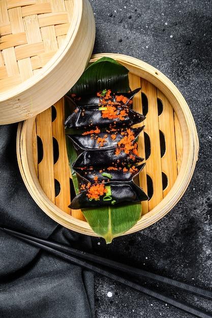 Schwarze dim-sum-knödel im bambusdampfer. asiatische küche Premium Fotos
