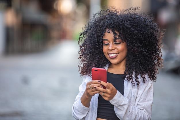 Schwarze frau des jungen lockigen haares, die mit handy geht. sms auf der straße. große stadt. Premium Fotos