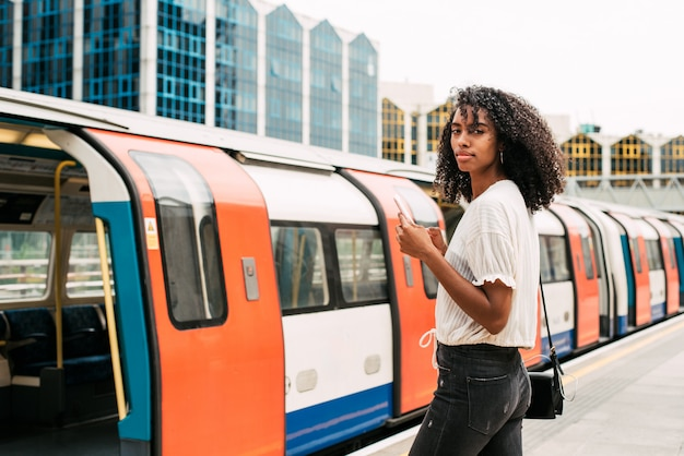 Schwarze frau, die handy bei london underground verwendet Premium Fotos