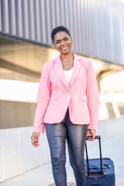 Schwarze frau, die mit der reisetasche trägt rosa jacke geht. Premium Fotos