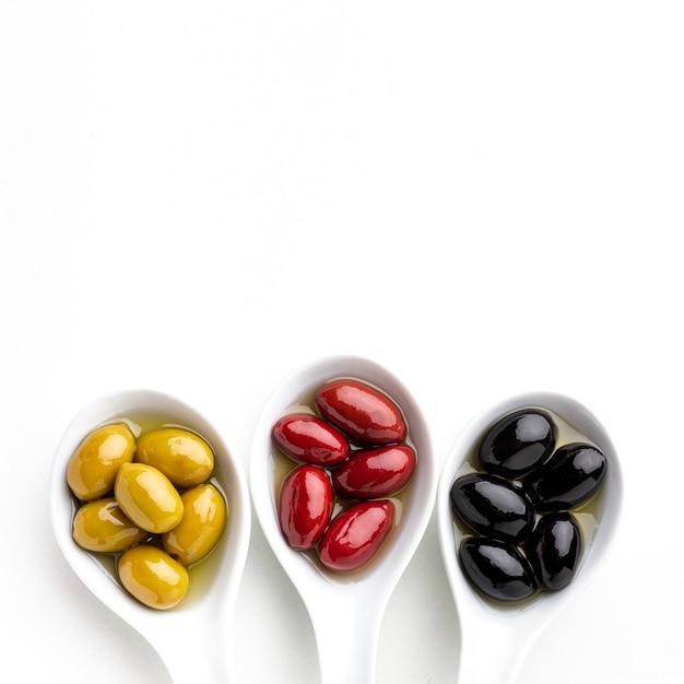 Schwarze gelbe rote oliven in den löffeln mit kopienraum Kostenlose Fotos