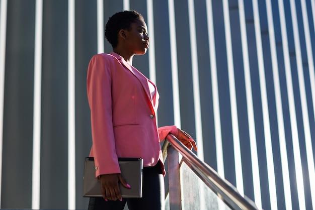 Schwarze geschäftsfrau, die nahes geschäftslokalgebäude steht. Premium Fotos