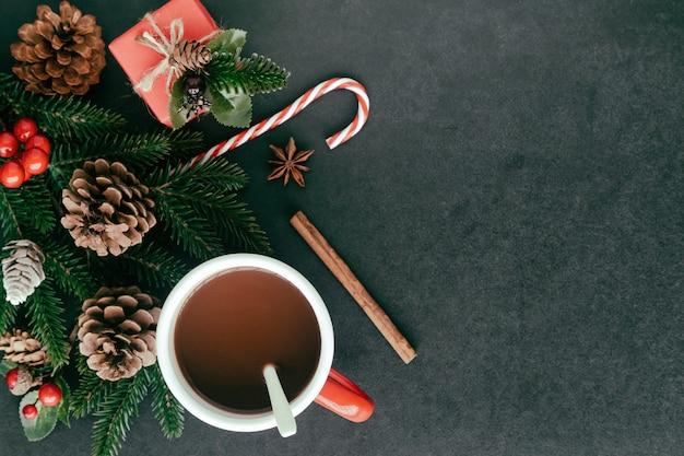 Schwarze granittabelle mit geschenkbox, kiefernblatt und kegeln, stechpalmenbällen und schale schokolade Premium Fotos