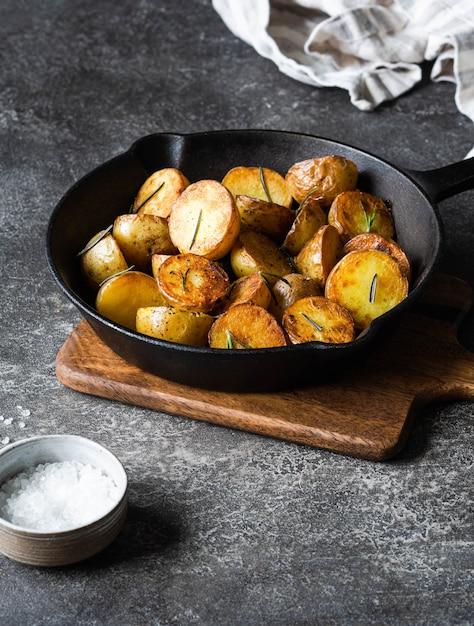 Schwarze gusseisenpfanne mit gebratenen bratkartoffelschnitzen mit kräutern auf dunkelgrauer oberfläche Premium Fotos