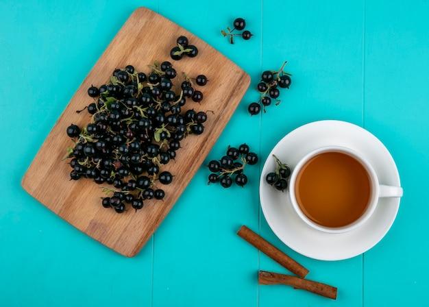 Schwarze johannisbeere der draufsicht auf einer tafel mit einer tasse tee und zimt auf einem hellblauen hintergrund Kostenlose Fotos