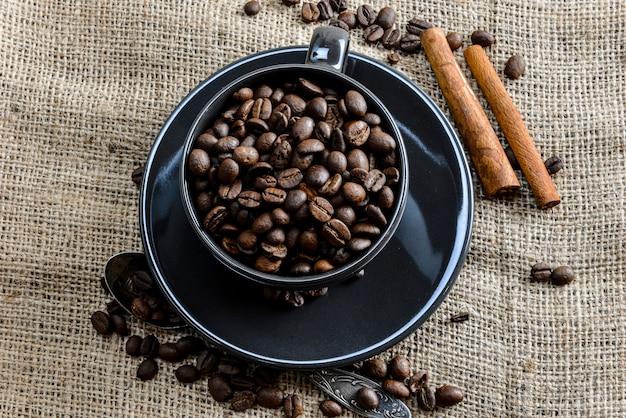 Schwarze kaffeetasse voller bio-kaffeebohnen und zimtstangen auf leinentuch Premium Fotos