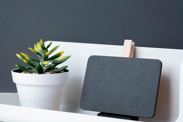 Schwarze klipptafel auf modernem bleistiftkasten und grünpflanze Premium Fotos