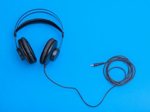 Schwarze kopfhörer mit aufgerollter schnur auf blauem hintergrund. Premium Fotos