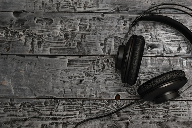 Schwarze kopfhörer mit draht auf schwarzem holztisch. Premium Fotos