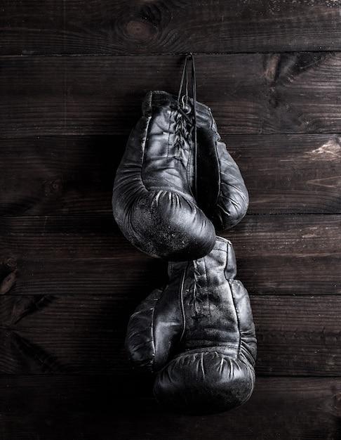 Schwarze lederne boxhandschuhe, die an einem nagel hängen Premium Fotos