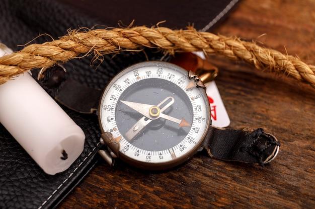Schwarze lederne geldbörse mit alter spielkarte und seil mit kompass Premium Fotos