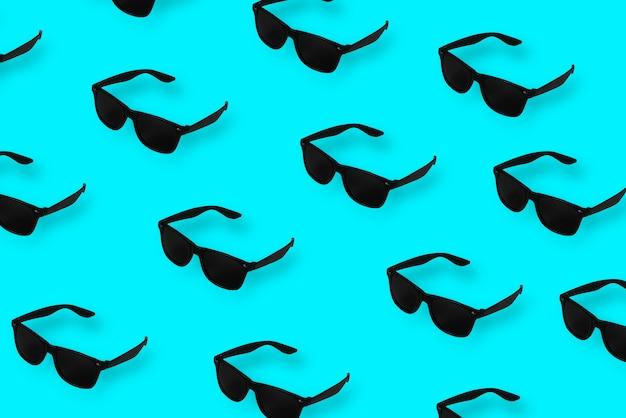 Schwarze mustersonnenbrille auf blauem pastellhintergrund Premium Fotos