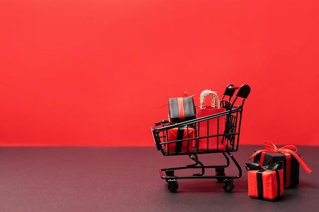 Schwarze papiertüten und geschenkboxen im einkaufswagen auf rot Premium Fotos
