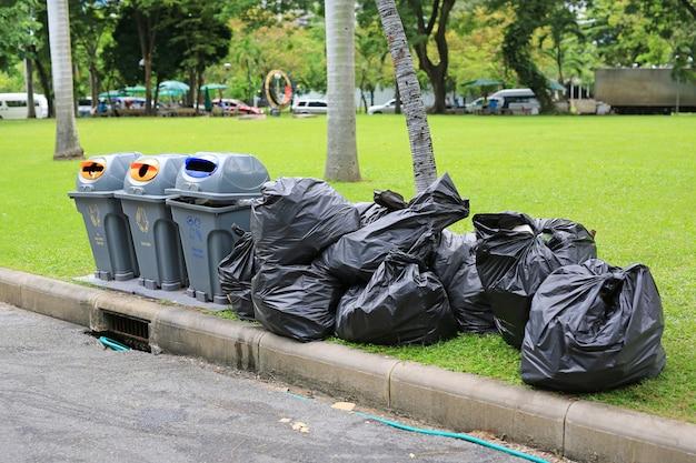 Schwarze plastikabfallsäcke auf garten des grünen grases nahe straße. Premium Fotos