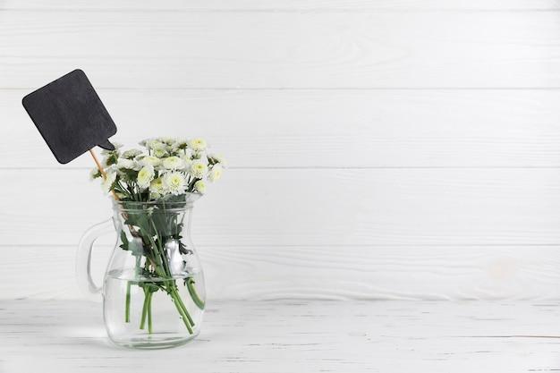 Schwarze rede und blumenstrauß der chrysantheme blüht im glasgefäß auf weißem holztisch Kostenlose Fotos