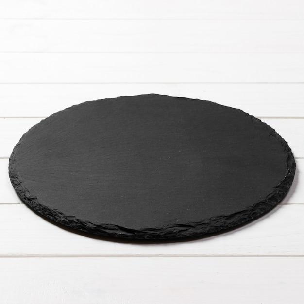 Schwarze runde platte auf hölzerner, draufsicht, kopienraum Premium Fotos