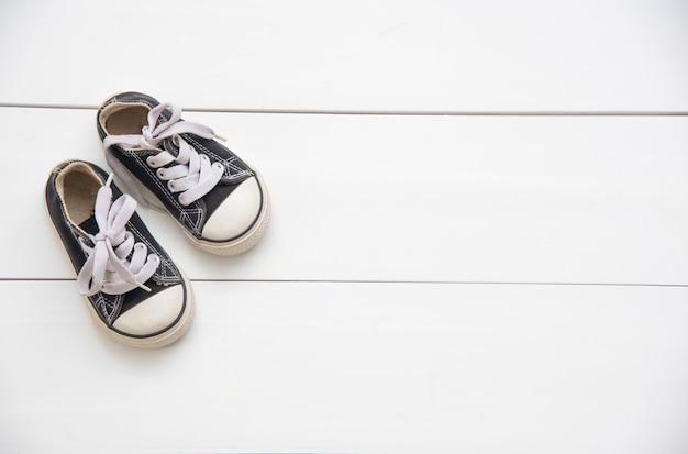 Schwarze schuhe für kinder auf holzfußboden Premium Fotos