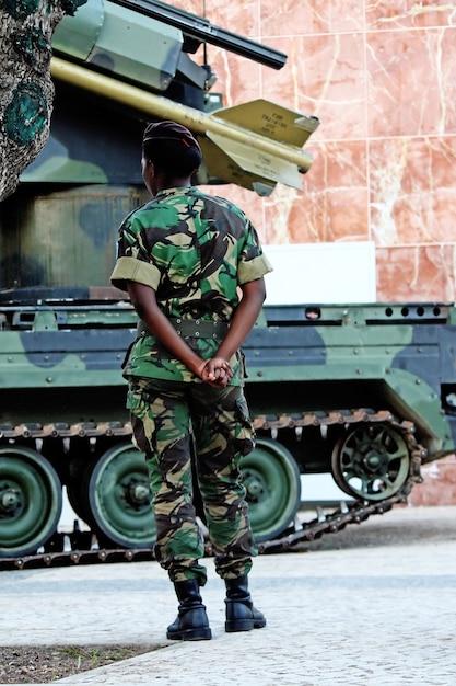 Schwarze soldatfrau, die nahe bei einem gepanzerten raketenfahrzeug steht. Premium Fotos