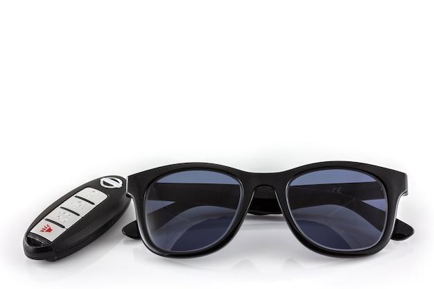Schwarze sonnenbrille und autoschlüssel im weißen hintergrund Premium Fotos
