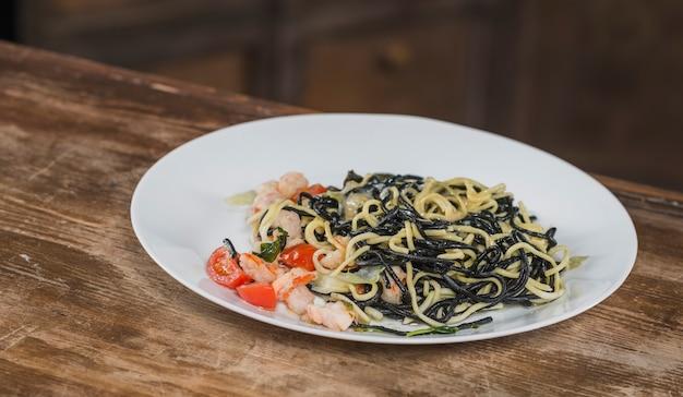 Schwarze spaghettis mit würzigen gemischten meeresfrüchten auf weißer platte Kostenlose Fotos