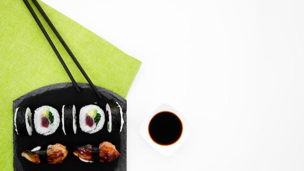 Schwarze steinplatte mit sushirollen auf einem weißen hintergrund Kostenlose Fotos