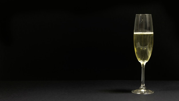Schwarze szene mit einem glas champagner. Kostenlose Fotos