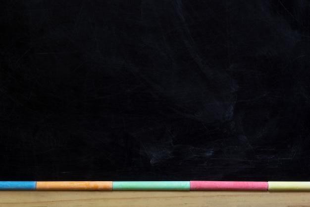 Schwarze tafel mit holzrahmen und farbkreiden. zurück zu schultafelhintergrund. kopieren sie platz Premium Fotos