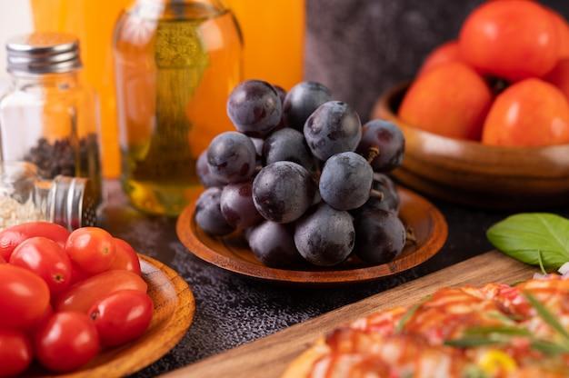 Schwarze trauben auf einem holzteller mit tomaten orangensaft und pizza. Kostenlose Fotos