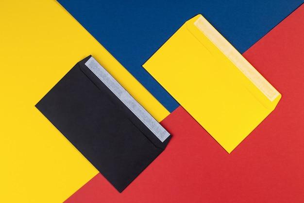 Schwarze und gelbe umschläge auf mehrfarbigem papierhintergrund. minimales konzept des geometriehintergrunds. mehrfarbiges papier mit umschlägen. kreatives flaches layout mit kopierraum. draufsicht Premium Fotos