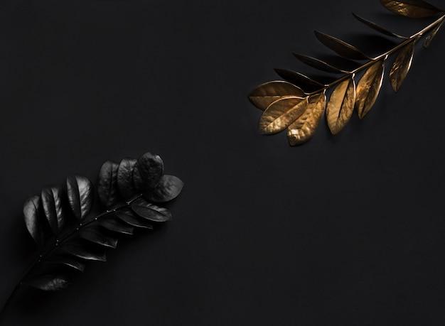 Schwarze und goldene pflanzen. natürliche breite horizontale blumendekoration mit draufsicht und kopierraum. Premium Fotos