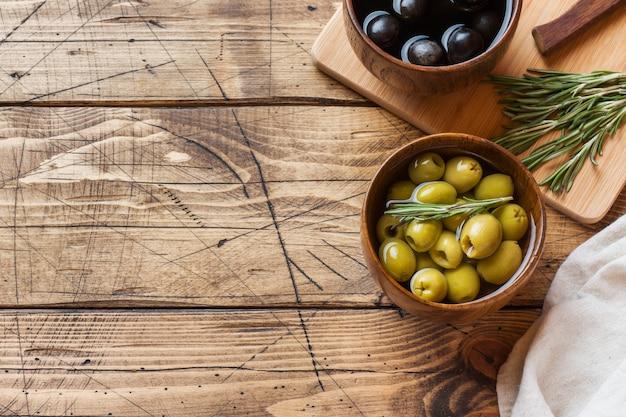 Schwarze und grüne oliven in den hölzernen schüsseln auf holztisch Premium Fotos