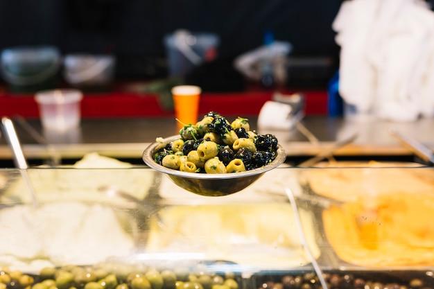 Schwarze und grüne oliven in der schüssel auf glaszähler Kostenlose Fotos