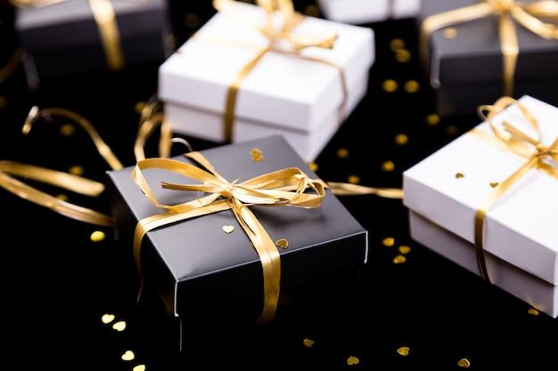 Schwarze und weiße geschenkboxen mit goldenem band auf glänzender oberfläche, Premium Fotos