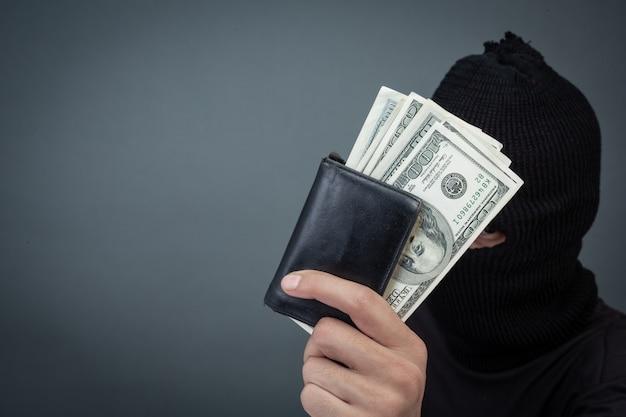 Schwarze verbrecher tragen ein hauptgarn, halten eine dollarkarte auf grau Kostenlose Fotos