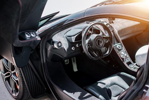 Schwarze vorderseitensalonansicht des sportwagens, schwarzes rad mit metallischer silberner farbe, richtung, tür offen. Kostenlose Fotos