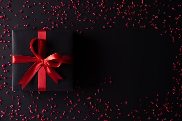 Schwarze weihnachtskästen mit rotem band auf schwarzem hintergrund. Premium Fotos