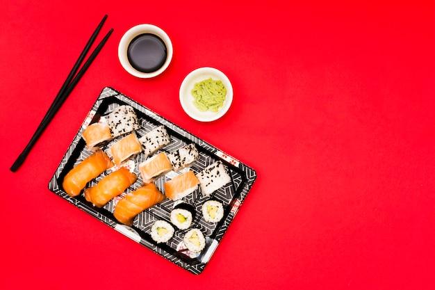 Schwarzer behälter füllte mit rollen nahe wasabi und sojasoße auf rotem zähler Kostenlose Fotos