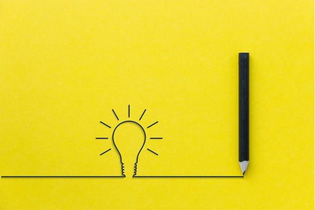 Schwarzer bleistift auf gelbem backgroud mit glühlampezeile Premium Fotos