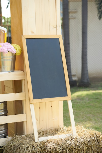 Schwarzer brettstand auf stroh verzieren mit blumenvase Premium Fotos