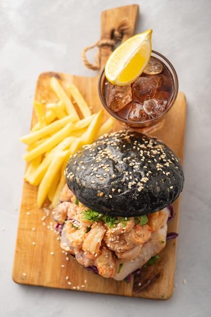 Schwarzer burger mit fischen und garnelen, fishburger mit garnelen, draufsicht. Premium Fotos