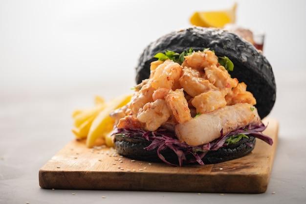 Schwarzer burger mit fischen und garnelen, fishburger mit garnelen über hellem hintergrund Premium Fotos