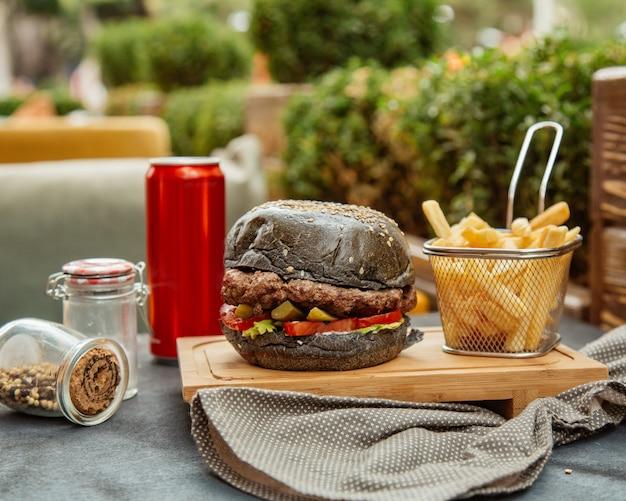 Schwarzer burger mit pommes und cola Kostenlose Fotos