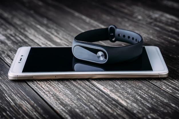 Schwarzer eignungsverfolger auf weißem smartphone auf holztisch Premium Fotos