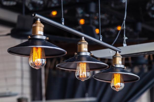 Schwarzer eisendachbodenleuchter mit edison-lampen auf einem schwarzen hintergrund, bokeh. Premium Fotos