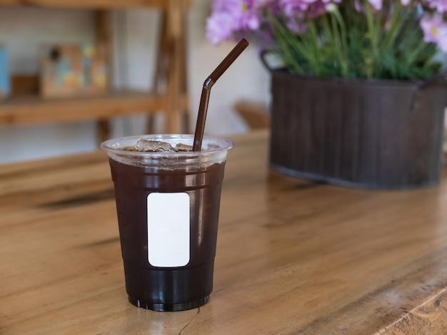 Schwarzer eiskaffee auf hölzerner tabelle im café Premium Fotos