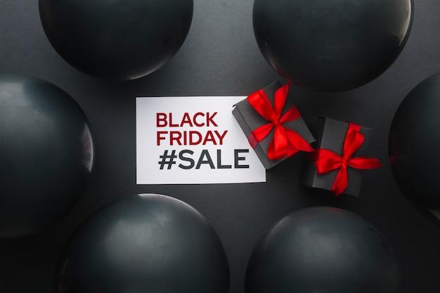 Schwarzer freitag geschenke, umgeben von schwarzen luftballons Kostenlose Fotos