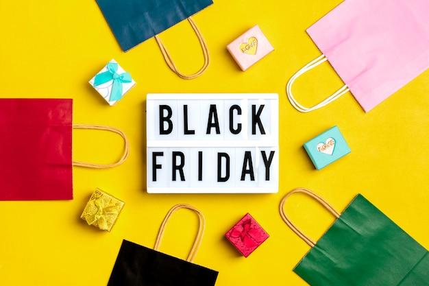 Schwarzer freitag-hintergrund mit mehrfarbigen verpackungstaschen mit geschenkboxen Premium Fotos