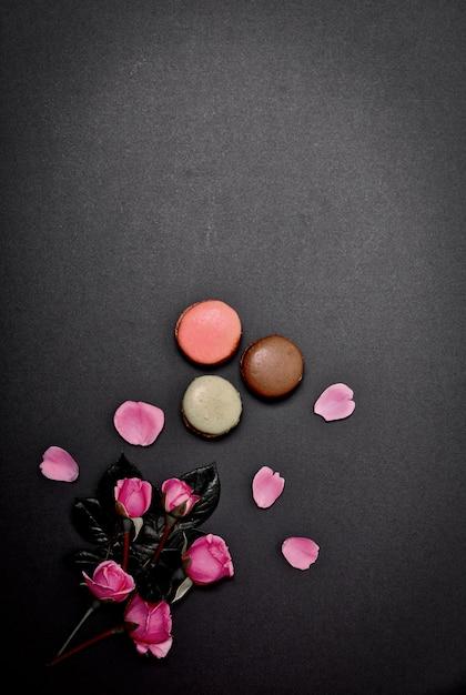 Schwarzer hintergrund mit makronen und einem blumenstrauß von rosa rosen Premium Fotos