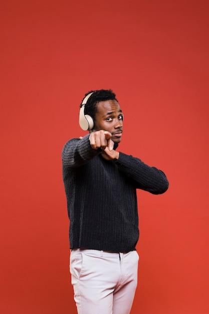 Schwarzer junge, der mit kopfhörern aufwirft Kostenlose Fotos